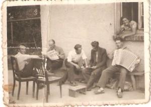Od lewej Eugeniusz Derengowski, Marian Gładysz , drugi odprawej Witold Dymiński, zakordeonem Tadeusz Galas woknie Alfreda Wiśniewska. Podwórko państwa Wiśniewskich . Domacyno